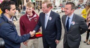Left to right:  Edward Gill from Tipperary and Killian O'Donnell from Clare speak to Taoiseach Enda Kenny and Brian Hayes canvassing commuters for at the Luas Terminal on St Stephens Green in Dublin recently. Photograph: Collins