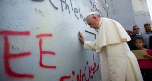 Pope Francis touches the wall that divides Israel from the West Bank, on his way to celebrate a mass in Manger Square next to the Church of the Nativity in the West Bank city of Bethlehem. Photograph: Reuters