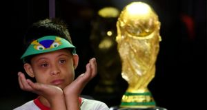 A Brazilian boy looks at the FIFA World Cup trophy on display at an exhibition in Brasilia, Brazil. Photograph: Fernando Bizerra/EPA