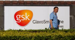 A file photograph showing a security guard walking past the GlaxoSmithKline (GSK) company sign outside the GSK factory in Shanghai. Photograph: EPA
