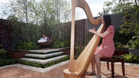 Harpist Niamh Humphreys from Kilmainham plays at the garden @You Talk I'll Listen' by Andrew Christophher Dunne as Emma Laura Skelton (L) reads in the background. Photograph: Gareth Chaney Collins