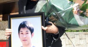 "Fujie Sugiyama holds a portrait of her son Takanori after he  was recognised as a victim of ""karoshi"" or death by overwork. Photograph: AFP/Getty Images"