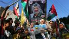 Palestinians in the Gaza Strip hold pictures of Yasser Arafat  and Palestinian president Mahmoud Abbas as they celebrate the announcement of the unity government  yesterday. Photograph:  Ibraheem Abu Mustafa/Reuters