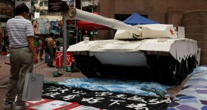 A shopper stands in front of a mock tank made by university students, imitating those used during the military crackdown on the pro-democracy movement at Beijing's Tiananmen Square in 1989, during an exhibition in Hong Kong. China has defended the crackdown ahead of the 25th anniversary. Photograph: Bobby Yip/Reuters.