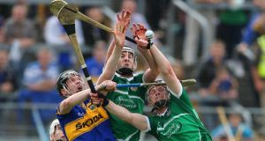 Tipperary's Thomas Stapleton contests possession with Donal O'Grady and Kevin Downes of Limerick. Photograph: Cathal Noonan/Inpho