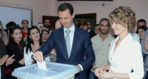 Syrian president Bashar al-Assad  and his wife Asma al-Assad cast their votes in the presidential elections at martyr Na'em Ma'asarani School in al-Malki neighborhood in Damascus yesterday. Photograph: EPA/Sana