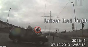 A screen grab from an on-board camera shows a motorist breaking a red light in front of a Luas tram.
