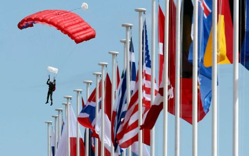 A paratrooper lands on Sword Beach near international flags during a D-Day celebration rehearsal in Ouistreham, on the Normandy coast. Some 18 heads of state will attend ceremonies bringing together 3,000 veterans in Normandy where Allied forces landed on June 6th, 1944 in a seaborne invasion that sped up the defeat of Nazi Germany in World War Two.  Photograph: Christian Hartmann/Reuters