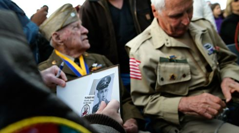 A young French boy holds photos from the 1940's to be autographed by 95-year-old World War II veteran Raymond W. Sylvester (L), who was with the 86th Chemical Mortar Battalion, and 91-year-old Warren Wilt (R) from the 82nd Airborn Division, during a ceremony honoring those who fought in the Normandy campaign on the day before the 70th anniversary of D-Day . Photograph Win McNamee/Getty Images