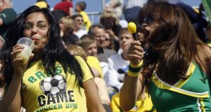 A Brazilian football fan enjoys the typical Brazilian drink, caipirinha, while dancing the samba with another fan. Photograph: Antonio Scorza/AFP