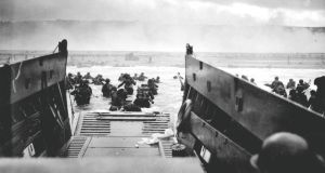 Troops wade ashore from a landing craft at Omaha Beach during the Normandy D-Day landings on June 6th, 1944. Photograph: Robert F. Sargent/US National Archives/Handout via Reuters.