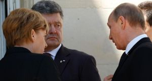 Ukraine president-elect Petro Poroshenko (second from left), German chancellor Angela Merkel and Russian President Vladimir Putin talk after a group photo during the 70th anniversary of the D-Day landings in Benouville yesterday. Photograph: Reuters/Kevin Lamarque
