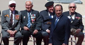 French president François Hollande awaits the arrival of foreign dignitaries as WWII veterans sit in the background during an international ceremony marking the 70th anniversary of the Allied landings on D-Day on Sword Beach in Ouistreham, in Normandy, France, yesterday. Photograph: EPA/Ian Langsdon