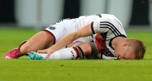 Germany's Marco Reus lies injured on the pitch during the international friendly between Germany and Armenia at the Coface Arena in Mainz. Photograph:  Thomas Eisenhuth/EPA