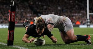 Conrad Smith of the All Blacks scores a late try against England despite Joe Marler's best efforts  at Eden Park   in Auckland. Photograph:   Simon Watts/Getty Images