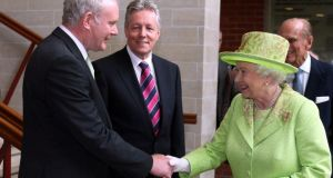 Queen Elizabeth and Northern Ireland  Deputy First Minister Martin McGuinness shake hands, watched by First Minister Peter Robinson, at the Lyric Theatre, Belfast, in June 2012. Photograph: Paul Faith/Getty Images