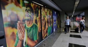 People arrive past a large banner with images of Brazil fans at the international airport in Curitiba. Photograph: Reuters