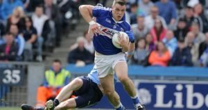 Laois' John O'Loughlin escapes the clutches of Dublin'sMichael Darragh Macauley. Photograph: Morgan Treacy/Inpho