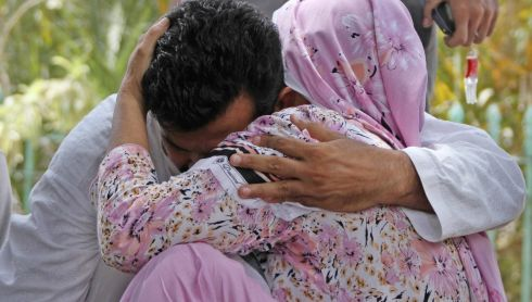 Relatives of missing Airport Security Force personnel comfort each other as they wait for the updates on the attack on Jinnah International Airport in Karachi. Photograph: Rehan Khan/EPA