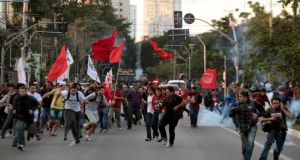 People run away from tear gas fired by police during the fifth day of metro workers' protest in Sao Paulo. Photograph: Reuters