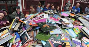 People  browse beside a skip filled with new books which are being cleared from the   former Bookworm bookshop in Bishop Street in Derry. Photograph: Trevour McBride