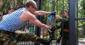 Pro-Russian separatists of the self-proclaimed Luhansk People's Republic remove the state coat of arms of Ukraine from a gate of an administration building, in the eastern Ukrainian city of Luhansk. Photograph: Reuters/Shamil Zhumatov