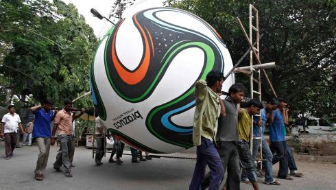 REFILE - CLARIFYING LOCATION Soccer fans carry a giant replica of the official ball for 2014 FIFA World Cup, made of fiber, in Kolkata June 11, 2014. Picture: Reuters