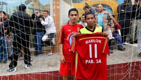 Prisoners Juan Valiente (L) and Barlok, wearing jerseys in the colours of Spain's national soccer team, pose for a photo after winning a soccer match as part of their own version of the 2014 World Cup at the Castro-Castro prison in Lima.Picture: Reuters