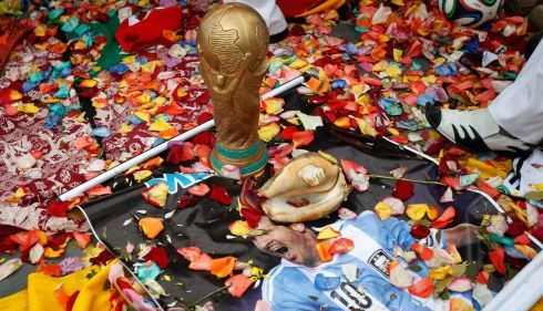 A poster of Argentina's soccer player Lionel Messi Iies on the ground next to a fake World Cup trophy as Peruvian shamans perform a ritual outside the National Stadium in Lima, June 10, 2014. The shamans are blessing the 2014 World Cup host nation Brazil and key soccer players good luck. Picture: Reuters