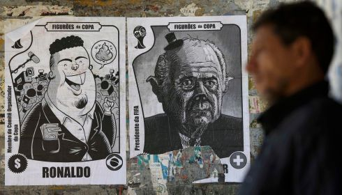 A man walks past posters with caricatures of (L-R) member of the FIFA World Cup 2014 Organizing Committee, former Brazilian soccer player Ronaldo, and FIFA President Sepp Blatter, in Brasilia. Picture: Reuters