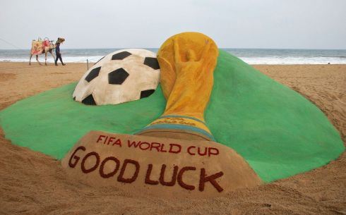 A man with his camel walks near a sand sculpture of 2014 World Cup, created by Indian sand artist Sudarshan Pattnaik at a beach in Puri, in the eastern Indian state of Odisha June 11, 2014.  Picture: Reuters