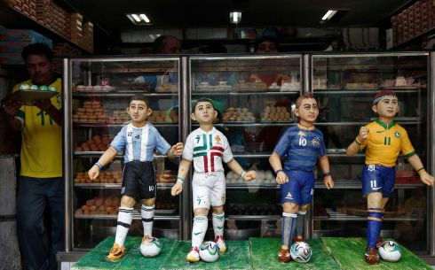 A worker carries sweets next to the models of soccer players that are made of sweets at a bakery shop ahead of the 2014 FIFA World Cup, on the outskirts of Kolkata. Picture: Reuters