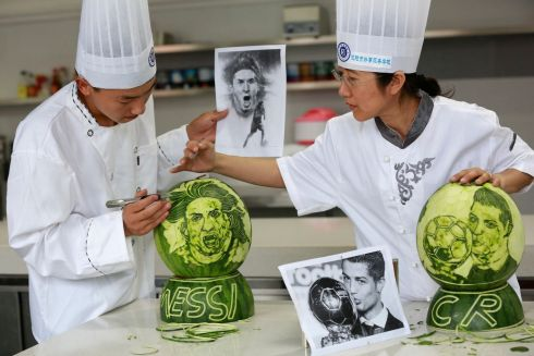 A culinary teacher (R) and a student carve images of Argentine soccer player Lionel Messi and Portugal's Cristiano Ronaldo on watermelons. Picture: Reuters