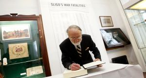 Retired Lieutenant Colonel Mark Scott signing the book of condolence at the News From The Past exhibition which is running up until the beginning of September in Sligo. Further information at newsfromthepast.ie