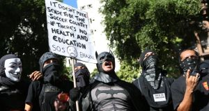 A person in a Batman costume holds a sign during a World Cup demonstration  in Rio de Janeiro, Brazil. Photograph: Joe Raedle/Getty Images