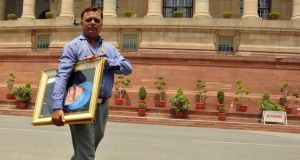 A man carries a portrait of India's former prime minister Manmohan Singh outside the parliament house building in New Delhi. New prime minister Narendra Modi has ordered civil servants to tidy up slovenly government offices in Delhi, requiring them to not only be uncluttered and litter free, but also sparkling. Photograph: Reuters