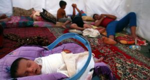 A baby sleeps with his family, who fled from the violence in Mosul, inside a tent yesterday at a camp on the outskirts of Arbil in Iraq's Kurdistan region. Photograph: Reuters/Azad Lashkari