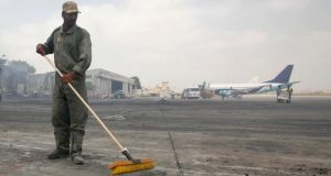 A man clears debris from the tarmac of Jinnah International Airport after last Sunday's attack by Taliban militants which triggered an all-night battle leading to at least 27 deaths. Photograph:  Athar Hussain/Reuters