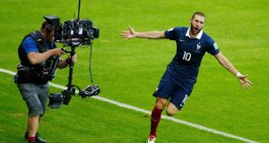 A television crew member films as France's Karim Benzema celebrates after scoring a goal during their 2014 World Cup Group E soccer match against Honduras at the Beira Rio stadium in Porto Alegre, June 15, 2014. REUTERS/Marko Djurica