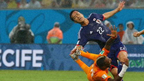 Ivory Coast's Geoffroy Serey Die (L) falls to the ground after being fouled by Japan's Maya Yoshida during their 2014 World Cup Group C soccer match at the Pernambuco arena in Recife, June 14, 2014.  REUTERS/Stefano Rellandini