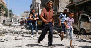 People flee a damaged site hit by what activists said was a barrel bomb dropped by forces loyal to Syria's president Bashar al-Assad in Aleppo's al-Sukari district yesterday. Photograph: Reuters/Hosam Katan