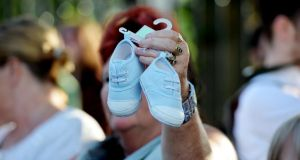 An infant's  shoes are held up at  a march of 300 people from the Department of Children and Youth Affairs on Mespil Road to Government Buildings to protest about the death of babies at the Tuam mother-and-baby home.  Photograph: Alan Betson