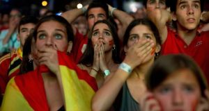 Spanish fans react while watching their team play against the Chileans. The current football World Cup champion have been eliminated from the competition after losing their second match 2-0. Photograph: Gonzalo Arroyo Moreno/Getty Images)