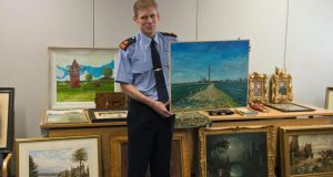 Supt Paul Moran at Pearse Street Garda station holding a painting by artist Mick O'Dea during a viewing of 48 pieces of stolen art. Photograph: Brenda Fitzsimons/The Irish Times