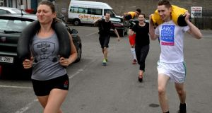 Gym member Zofia Siok with Ciarán D'Arcy running with sandbags. Photograph: David Sleator
