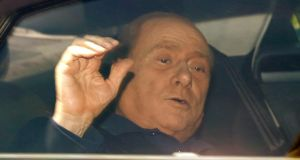 Silvio Berlusconi waves from his car as he leaves the Sacra Famiglia' community in Cesano Boscone, near Milan, yesterday. Photograph: AP Photo/Luca Bruno