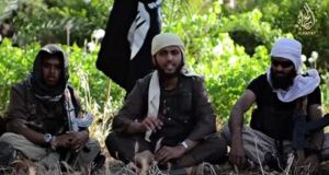 An Islamist fighter, centre, identified as Abu Muthana al-Yemeni from Britain, speaks from an unknown location in an Isis video urging fellow Britons to join. Photograph: Reuters TV