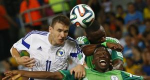 Bosnia's Edin Dzeko beats   Nigeria's Kenneth Omeruo (22) and Shola Ameobi to the ball as he misses a chance to score a goal during their 2014 World Cup Group F soccer match at the Pantanal arena in Cuiaba. Photograph: Michael Dalder/Reuters