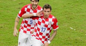 Croatia's Mario Mandzukic celebrates with  team-mate Vedran Corluka after scoring against  goal during the group A World Cup soccer match between  Cameroon.