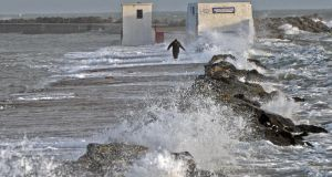 A solitary figure battles with high wind and waves , on the Great South Wall, at Poolbeg last December.  Insurance claims relating to storm damage and flooding last winter was about €156 million, according to the Irish Insurance Federation. Photograph: Eric Luke/The Irish Times